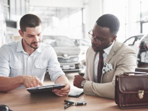 A young attractive black businessman buys a new car, he signs a contract and takes the keys to the manager.